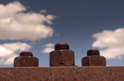 Trois écrous rouillés - et - boulons sur le pont avec le ciel bleu Photographie stock libre de droits