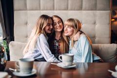 Trois étreintes attrayantes d'amies ensemble en café Images stock