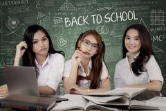 Trois étudiantes s'asseyent dans la classe Photographie stock
