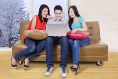 Trois étudiants à l'aide de l'ordinateur portable dans le divan Photos libres de droits