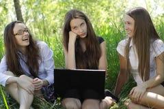 Trois étudiants avec le cahier en stationnement Photographie stock
