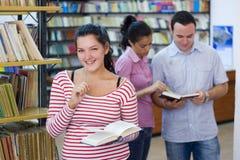 Trois étudiants dans la bibliothèque Photo stock