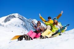 Trois étudiants dans la neige avec des surfs des neiges Photos stock