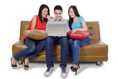 Trois étudiants et ordinateurs portables sur le divan Photographie stock libre de droits