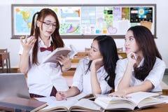 Trois étudiants féminins discutant dans la classe Photos libres de droits