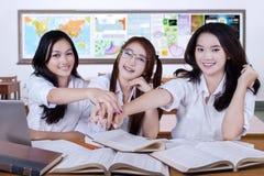 Trois étudiants joignant des mains dans la classe Photo stock