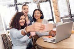 Trois étudiants joviaux prenant le selfie pendant l'étude Images libres de droits