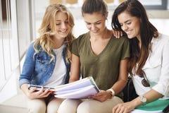Trois étudiants occupés sur le campus Photo stock