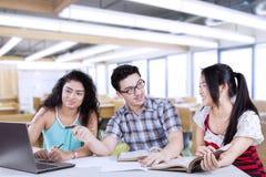Trois étudiants parlant dans la classe Photographie stock