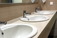 Trois éviers blancs dans la salle de toilette image stock