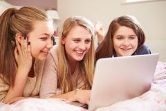 Trois adolescentes à l'aide de l'ordinateur portable dans la chambre à coucher Image stock