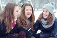 Trois adolescentes ayant l'amusement dans la neige Photos stock