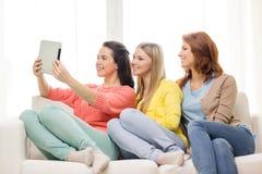 Trois adolescentes de sourire avec le PC de comprimé à la maison Images stock