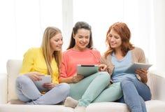 Trois adolescentes de sourire avec le PC de comprimé à la maison Photographie stock libre de droits