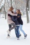 Trois adolescentes jouant dans la neige Image stock