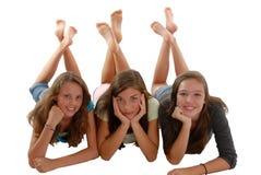 Trois adolescentes s'étendant sur le menton d'étage à disposition Image stock