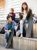 Trois adolescents avec des smartphones Photographie stock