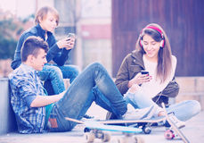 Trois adolescents avec des smartphones Photographie stock libre de droits