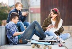 Trois adolescents avec des smartphones dedans dehors Photo stock