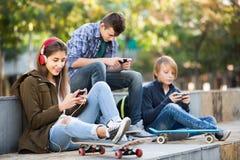 Trois adolescents avec des smartphones dedans dehors Photographie stock libre de droits