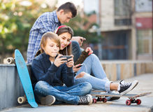 Trois adolescents avec des smartphones dedans dehors Photographie stock