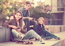 Trois adolescents avec des smartphones dedans dehors Photos stock