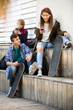 Trois adolescents avec des téléphones dehors Photos libres de droits