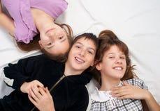 Trois adolescents de sourire se trouvant sur le bâti tête à tête Photo stock