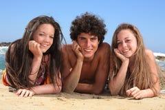 Trois adolescents heureux sur la plage Images stock
