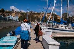 Trois adultes marchant loin sur un dock après des bateaux images stock