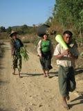Trois agriculteurs marchant de retour la maison du champ portant le produit frais image libre de droits