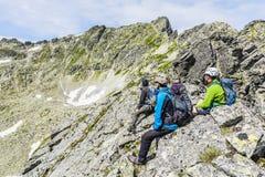Trois alpinistes se reposant sur l'arête Images stock