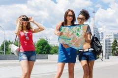 Trois amie dehors avec la carte de papier de ville Photo stock