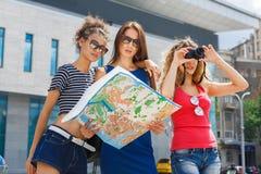 Trois amie dehors avec la carte de papier de ville Photo libre de droits