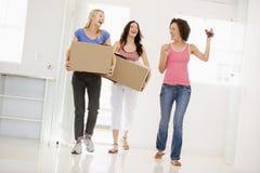 Trois amie entrant dans le sourire à la maison neuf Photo stock