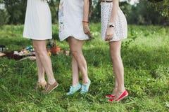 Trois amie portant des robes de blanc en bois Images stock