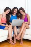 Trois amies aux pieds nus de jeunes s'asseyant sur le sofa avec l'ordinateur portable, La Image libre de droits