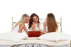 Trois amies avec l'ordinateur portable. Images stock