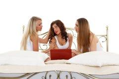 Trois amies avec l'ordinateur portable. Photos stock