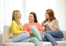 Trois amies ayant un entretien à la maison Image stock