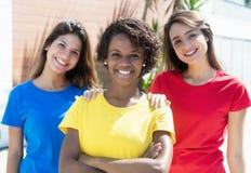 Trois amies d'afro-américain et de Caucasien dans le shi coloré Image libre de droits