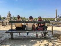 Trois amies de femmes s'asseyent sur le banc de Tuileries faisant face à Place de la Concorde, Paris, France Image stock