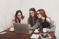 Trois amies de jeunes femmes avec l'ordinateur portable Photographie stock