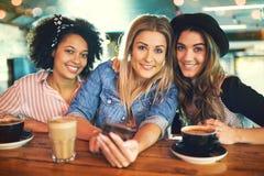 Trois amies de sourire attirantes de jeunes femmes Image stock