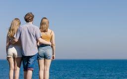 Trois amies des jeunes par l'océan de mer Images stock