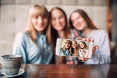 Trois amies fait le selfie sur l'appareil-photo en café Images libres de droits