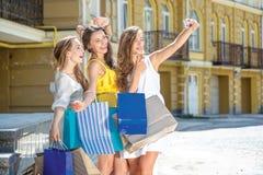 Trois amies font le selfie à un téléphone portable Filles tenant le sho Image libre de droits