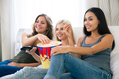 Trois amies heureuses mangeant du maïs éclaté et regardant la TV Image stock