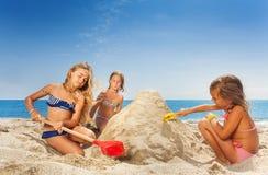 Trois amies heureux sculptant le pâté de sable Image stock
