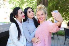 Trois amies merveilleuses de jeune fille font le selfie, photo sur le pho Image stock